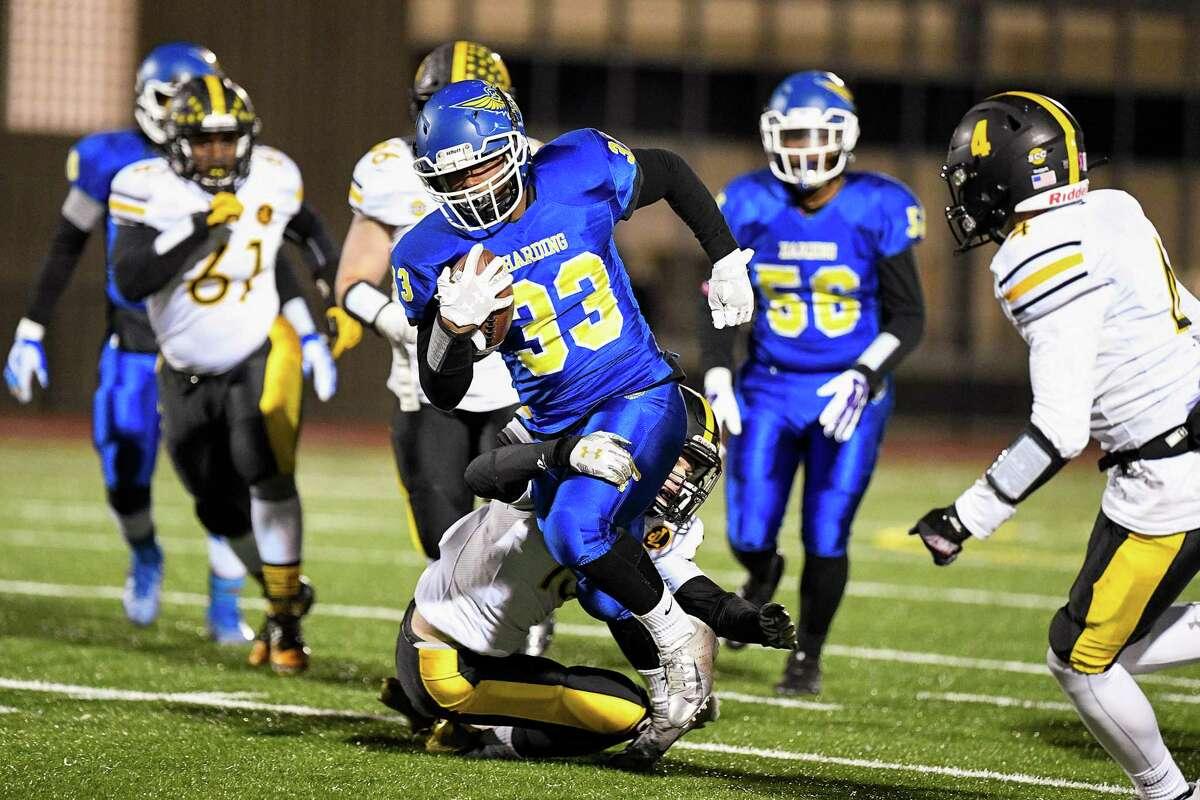 Harding High's Darnell Benoit breaks a tackle against Jonathan Law, at Harding High in Bridgeport, Friday, November 8, 2019