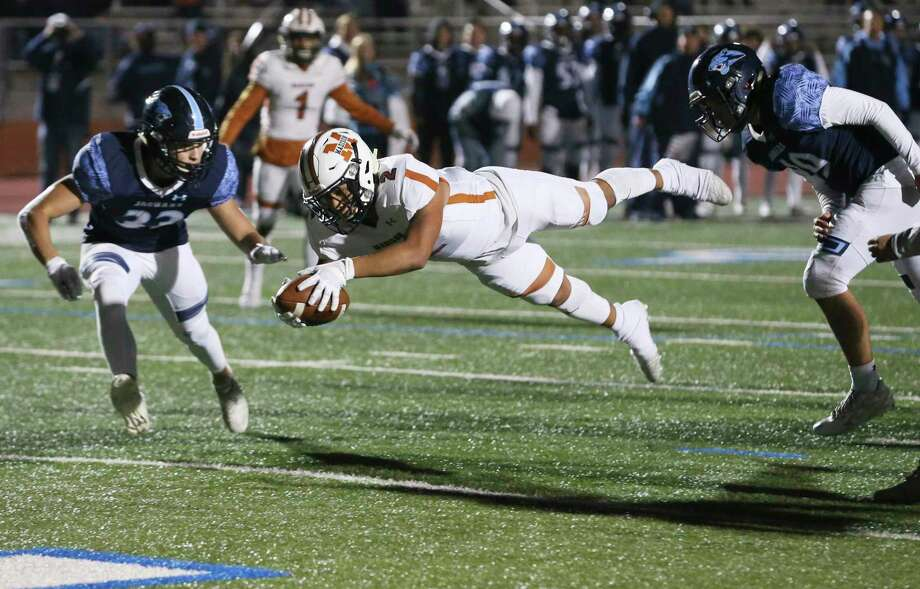 Madison's Darien Gill (02) dives in for a touchdown against Johnson's Kaleb Meza (33) and Djuan Hill (49) at their football game at Heroes Stadium on Friday, Nov. 8, 2019. (Kin Man Hui/San Antonio Express-News) Photo: Kin Man Hui, Staff / Staff Photographer / ©2019 San Antonio Express-News