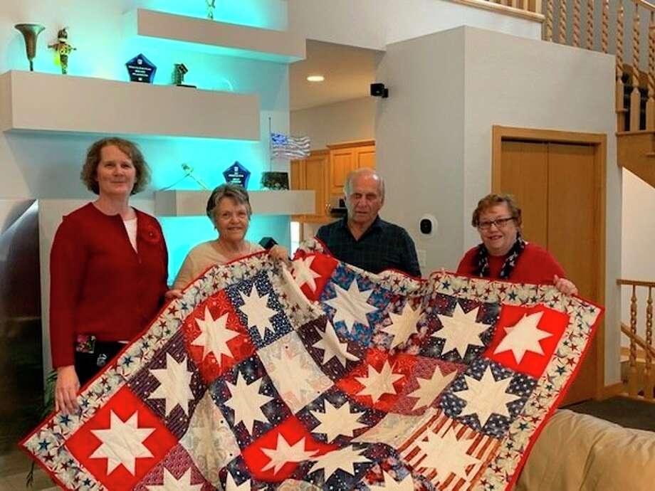 From left, Nancy Pnacek, Linda Fisher, Mike Pnacek and Karen Miller display a Quilt of Valor. (Photo provided)
