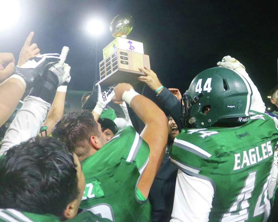 Members of the Pasadena Eagles hoist the Pride Bowl Trophy in the air Friday night, following their 26-21 win in the 56th annual game. Photo: Robert Avery