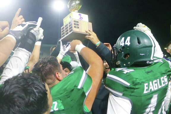 Members of the Pasadena Eagles hoist the Pride Bowl Trophy in the air Friday night, following their 26-21 win in the 56th annual game.