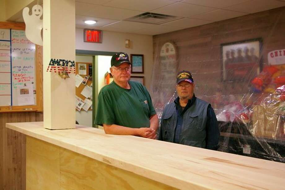 Bill Shelagowski and Joe DuFort, U.S. Army veterans and members of the VFW Chemical City Post No. 3651, stand in front of the bar that Shelagowski and others have constructed. This is one of many renovations taking place in the bar, or canteen, part of the building. (Photo by Niky House)