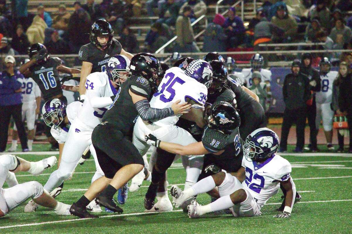 Angleton's J.T. Anderson (35) is wrestled down by Friendswood's Dane Roenne (10) and Jackson Stephens (35) Friday at Henry Winston Stadium.