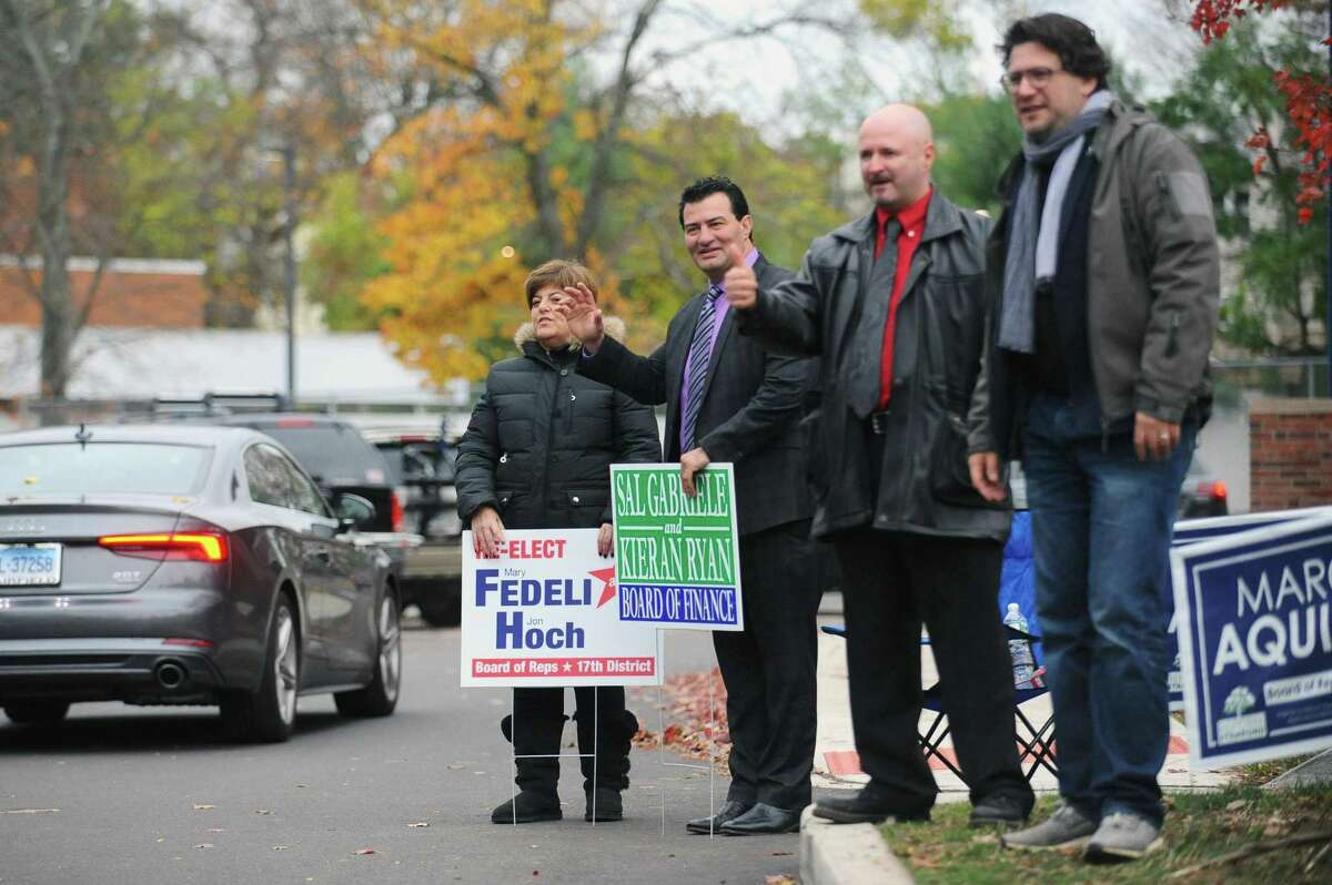 From left, Mary Fedeli, Sal Gabriele, Marc Aquila and David Michel wave to voters as they enter the parking lot of Springdale School in 2017. Gabriele, a Republican, is stepping down from the Board of Finance.