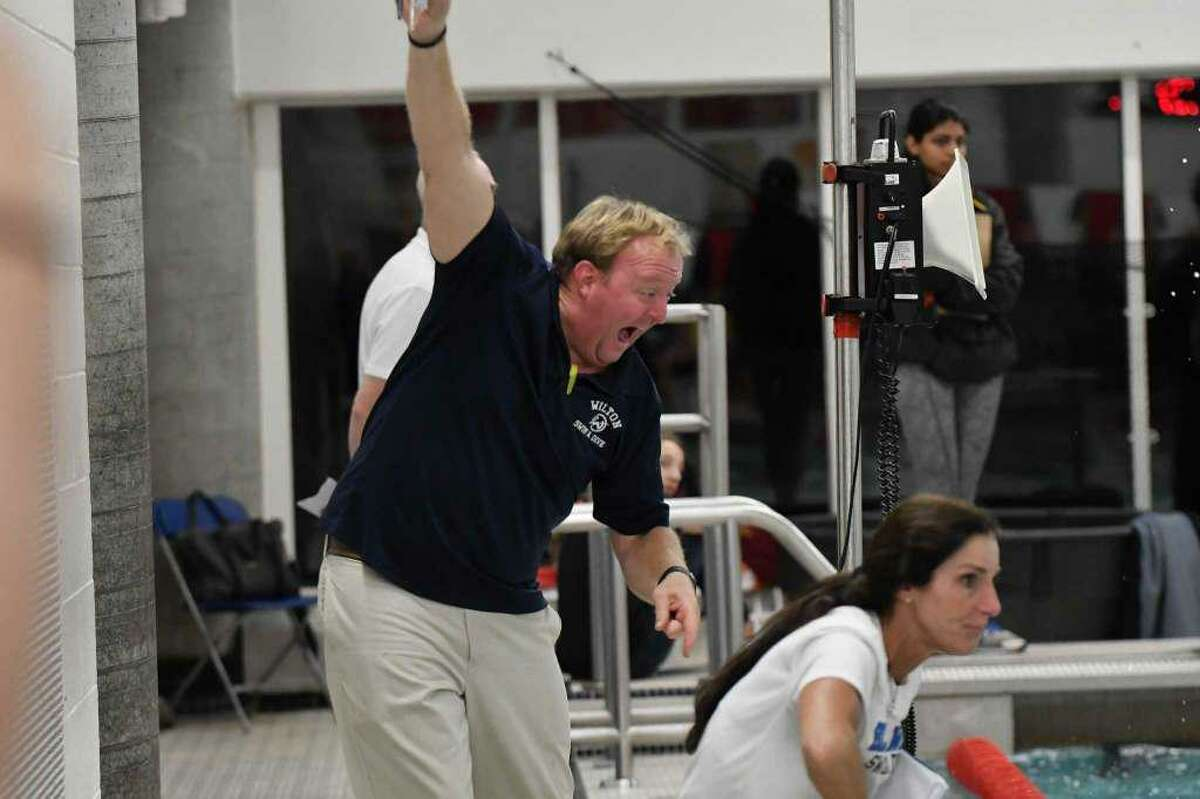 Wilton coach Todd Stevens does his best to motivate a swimmer at Tuesday's FCIAC girls swimming championship in Greenwich.