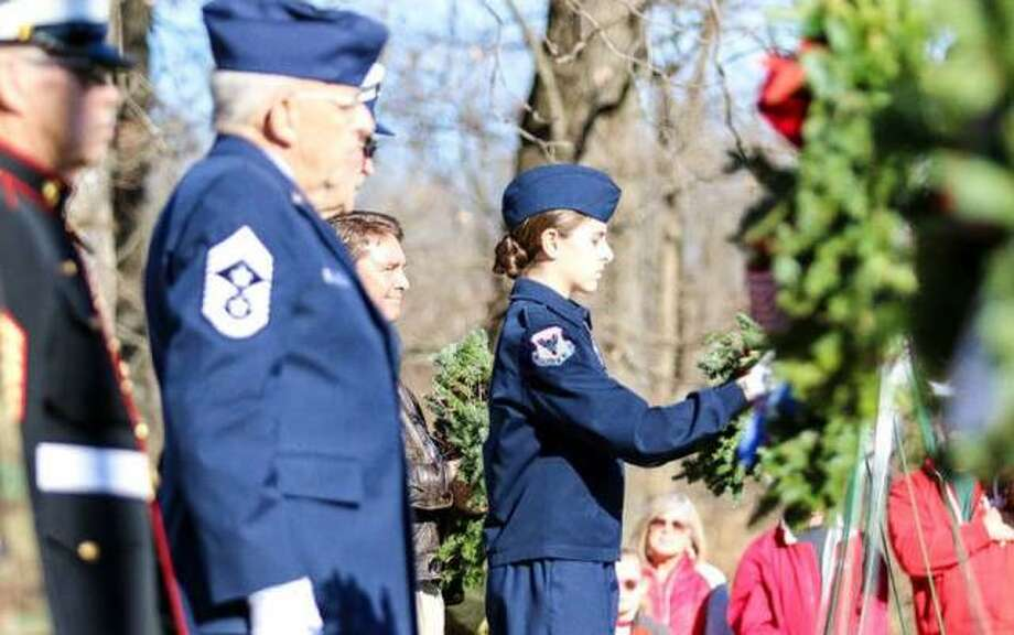 "In this file photo, participants help place some of the 560 wreaths on graves at Alton National Cemetery in 2017 as part of ""Wreaths Across America."" This year's program is planned for Dec. 14."