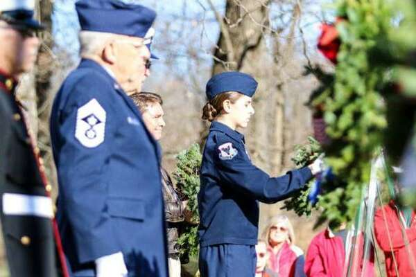 """In this file photo, participants help place some of the 560 wreaths on graves at Alton National Cemetery in 2017 as part of """"Wreaths Across America."""" This year's program is planned for Dec. 14."""