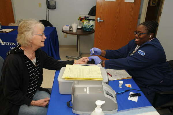 Gloria McGaughey of Godfrey gets a blood sugar screening from Sherell Dennis, a nursing student from Lewis and Clark Community College, during Saturday's Diabetes Fair at Alton Memorial Hospital.