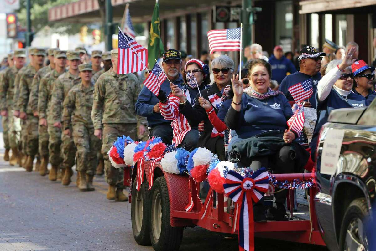 People on the Veterans of Foreign Wars Auxiliary, Department of Texas, District 20 float wave flags during the U.S. Veterans Day Parade Association's 20th annual Veterans Day parade through downtown San Antonio on Saturday, Nov. 9, 2019. (Kin Man Hui/San Antonio Express-News)