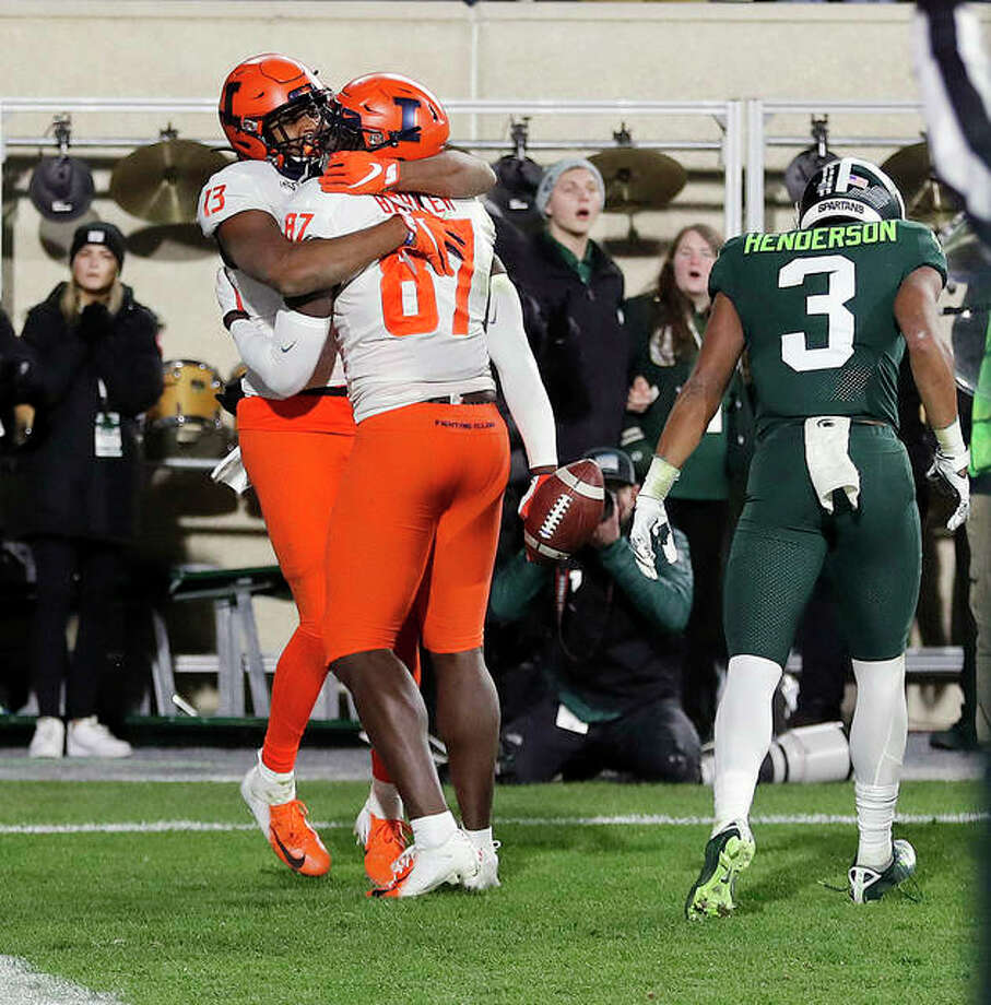Illinois wide receiver Caleb Reams (13) hugs teammate tight end Daniel Barker (87) after Baker scored in the closing seconds to defeat Michigan State Saturday in East Lansing, Mich. Photo: AP Photo