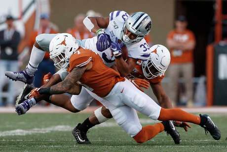 Caden Sterns (7) and Ayodele Adeoye (40) of the Texas Longhorns tackle Tyler Burns (33) of the Kansas State Wildcats in the fourth quarter at Royal-Memorial Stadium on Nov. 9, 2019 in Austin.