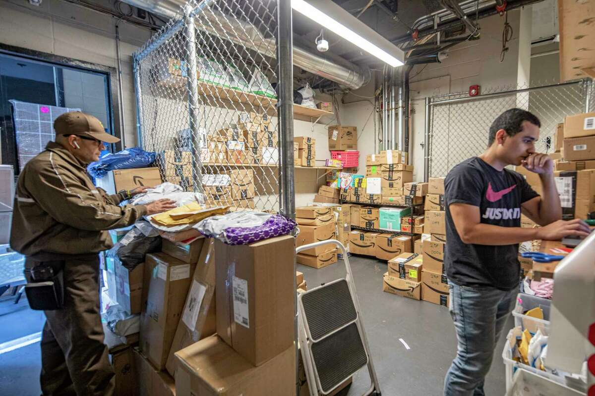 The package room on Oct. 29, 2019, at Riverbank, a high-rise in New York's Hella€™s Kitchen neighborhood, which can fill up quickly. Diego Ruiz, right, the assistant manager in charge of deliveries, uses Package Concierge, a locker system to get the packages to residents. (Tony Cenicola/The New York Times)