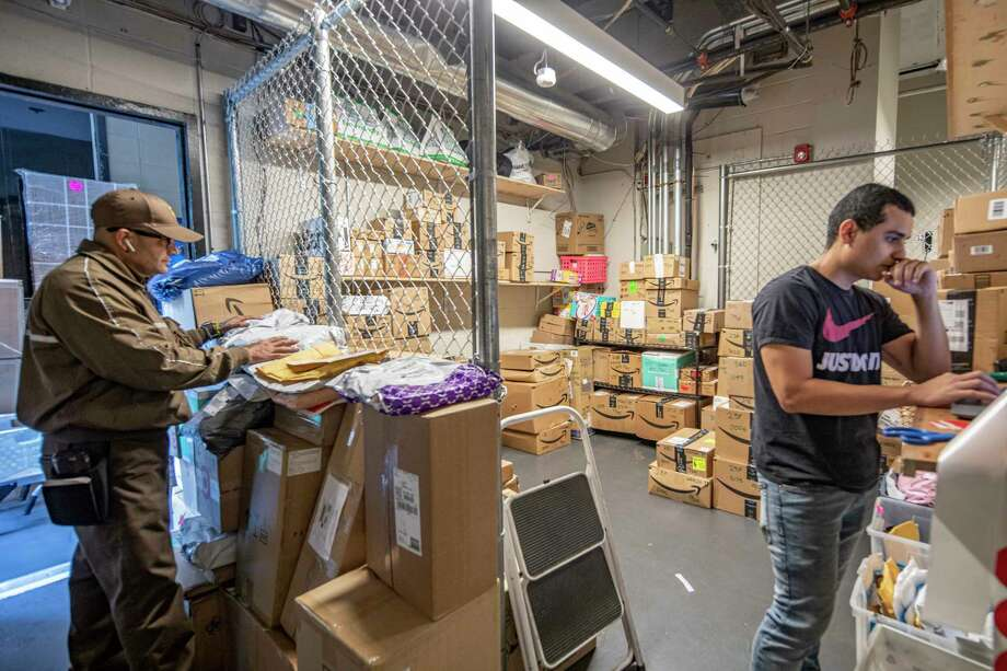 The package room on Oct. 29, 2019, at Riverbank, a high-rise in New York's Hella€™s Kitchen neighborhood, which can fill up quickly. Diego Ruiz, right, the assistant manager in charge of deliveries, uses Package Concierge, a locker system to get the packages to residents. (Tony Cenicola/The New York Times) Photo: TONY CENICOLA / NYTNS