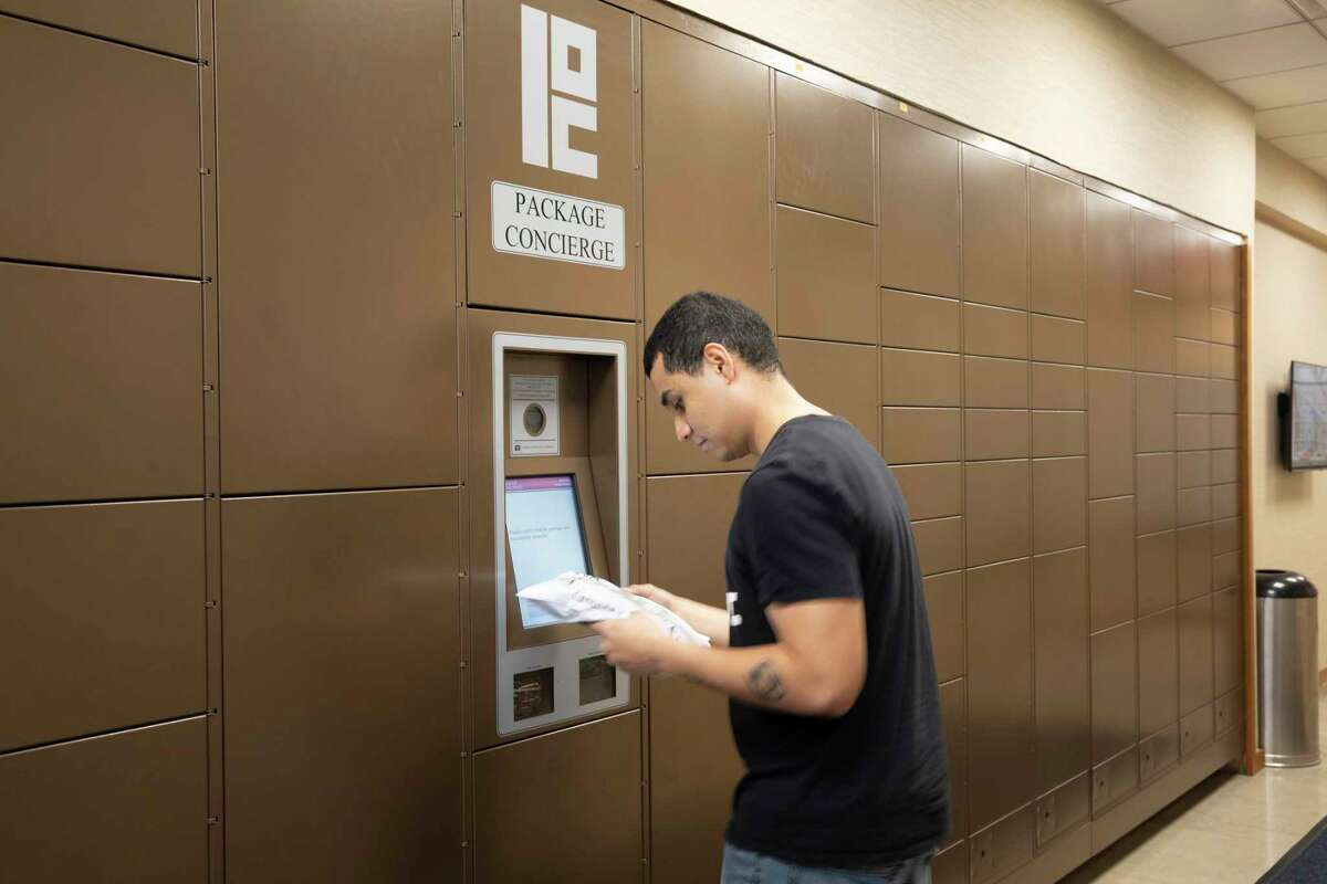 Diego Ruiz, the assistant manager in charge of deliveries, uses Package Concierge, a locker system to get packages to residents on Oct. 29, 2019, at Riverbank, a high-rise in New York. Package deliveries are overtaking New York City and the way many residential buildings have responded to the influx is to go high tech. (Tony Cenicola/The New York Times)