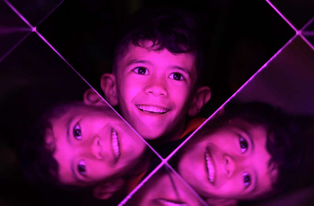 Justin Gonzales looks through the Kaleidoscope deLight designed by John Tyler and Abbie Hyche during Luminaria.