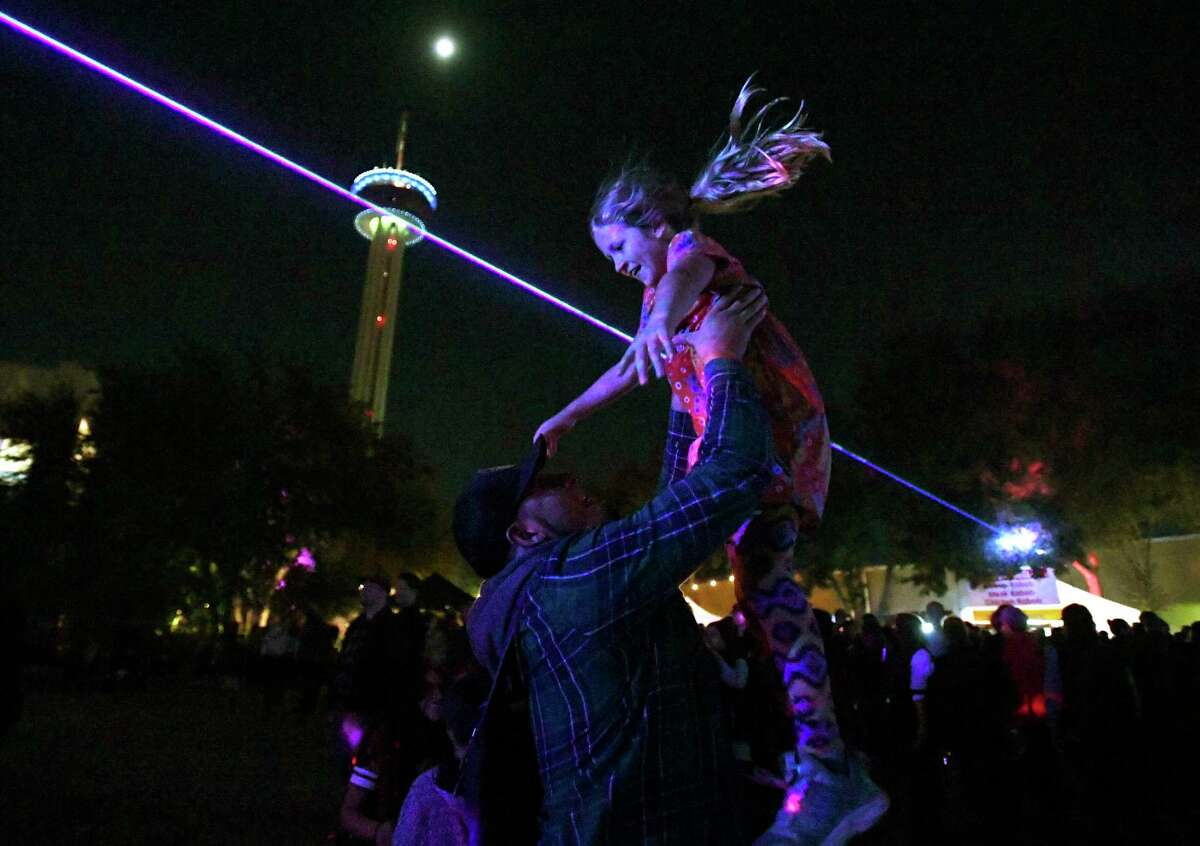 Olivia Barajas is tossed into the air during a laser light show by Hector Celestino de la Cruz during Luminaria.