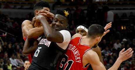 Chicago Bulls forward Chandler Hutchison, back, fights for the ball with Houston Rockets center Clint Capela (15) and guard Tomas Satoransky (31) during the first half of an NBA basketball game Saturday Nov. 9, 2019, in Chicago. (AP Photo/Matt Marton)