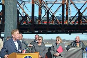 Governor Ned Lamont talks about needed transportation infrastructure improvements March 18 on Naugatuck Avenue in Milford. The focus of the talk was the Devon Bridge, in the distance, which carries New Haven line trains over the Housatonic River.