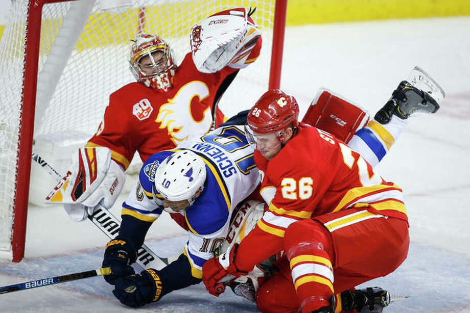 The Blues' Brayden Schenn (middle) is checked into Flames goalie David Rittich (left) by Michael Stone during the second period Saturday night in Calgary. Photo: Associated Press