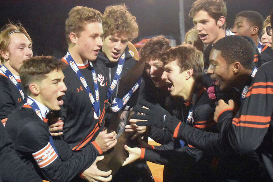 The Edwardsville boys soccer team celebrates with the Class 3A state tournament third-place trophy after defeating St. Patrick 3-2 on Saturday in Hoffman Estates.