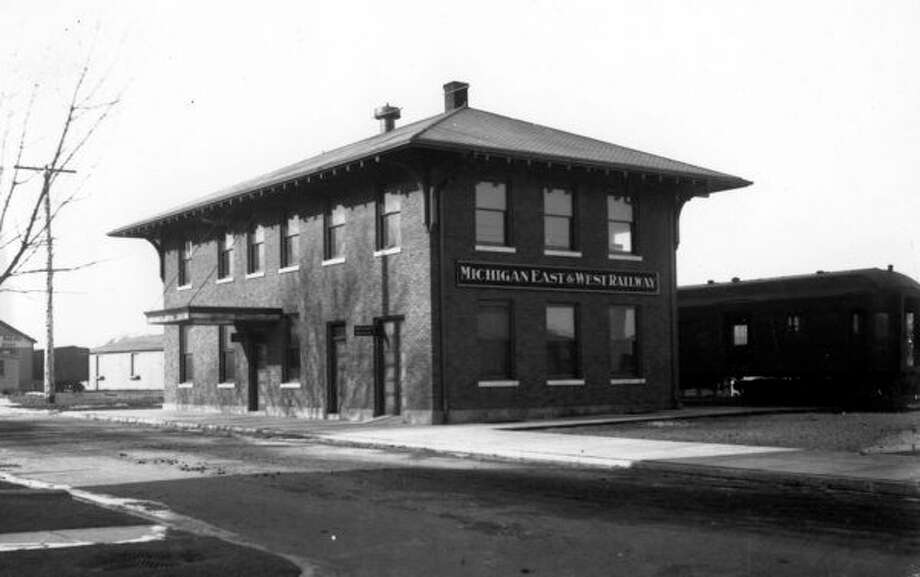 The Michigan East and West Railroad is shown in this 1915 picture and the building still stands today and was formerly the Johnson Funeral Home.