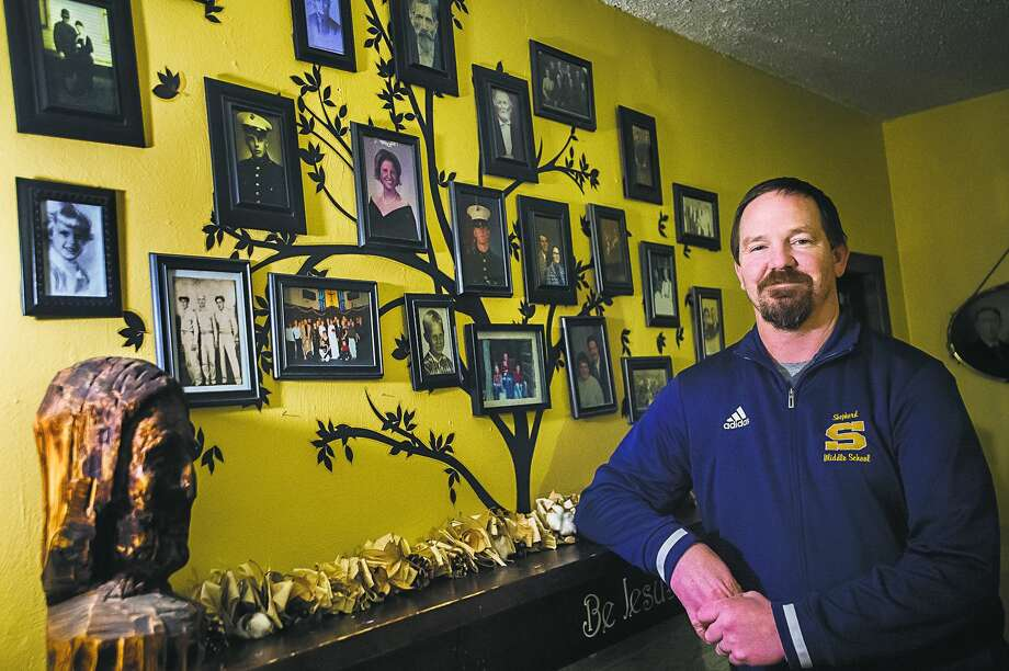 Midland's Dan TerBurgh poses near a wall dedicated to his family ancestry at his home. TerBurgh, who served two tours of duty during the Iraq War, recently began a new career as a middle school social studies teacher and eighth-grade boys' basketball coach after quitting his job and going to college in his mid-30s. Photo: Katykildee/kildee@mdn.net