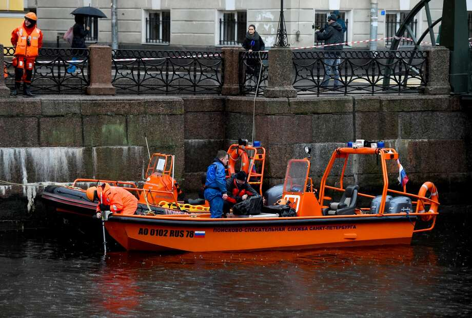 Journalist stand on the riverbank as they watch Russian emergency rescuers and police investigators conducting searches on the Moika River, in Saint Petersburg, on November 10, 2019, following the murder of a woman that implicates Russian historian Oleg Sokolov. - A prominent Saint Petersburg-based Napoleon expert has confessed to murdering his young lover and former student and dismembering her body in a grisly crime that sent shock waves across Russia. Oleg Sokolov, a 63-year-old history lecturer who received France's Legion d'Honneur in 2003, was arrested on November 10, 2019 on suspicion of murder after he was hauled out of Saint Petersburg's Moika River with a backpack containing a woman's arms. (Photo by OLGA MALTSEVA / AFP) (Photo by OLGA MALTSEVA/AFP via Getty Images) Photo: OLGA MALTSEVA/AFP Via Getty Images