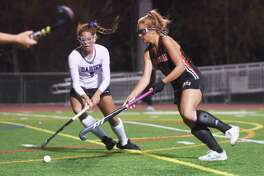 New Canaan's Anna Lindeis (18) and Darien's Raina Johns (9) battle for the ball during an FCIAC field hockey semifinal game at Brien McMahon in Monday, Nov. 4.