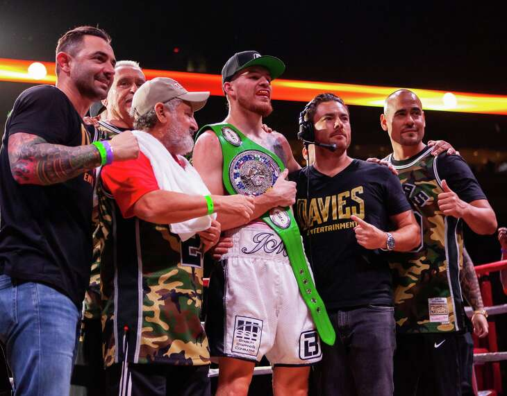 Eddie Ortiz Jr., white trunks, celebrates keeping his middleweight title by unanimous decision with his team on Saturday night at the Alamodome's Illusions Theater.