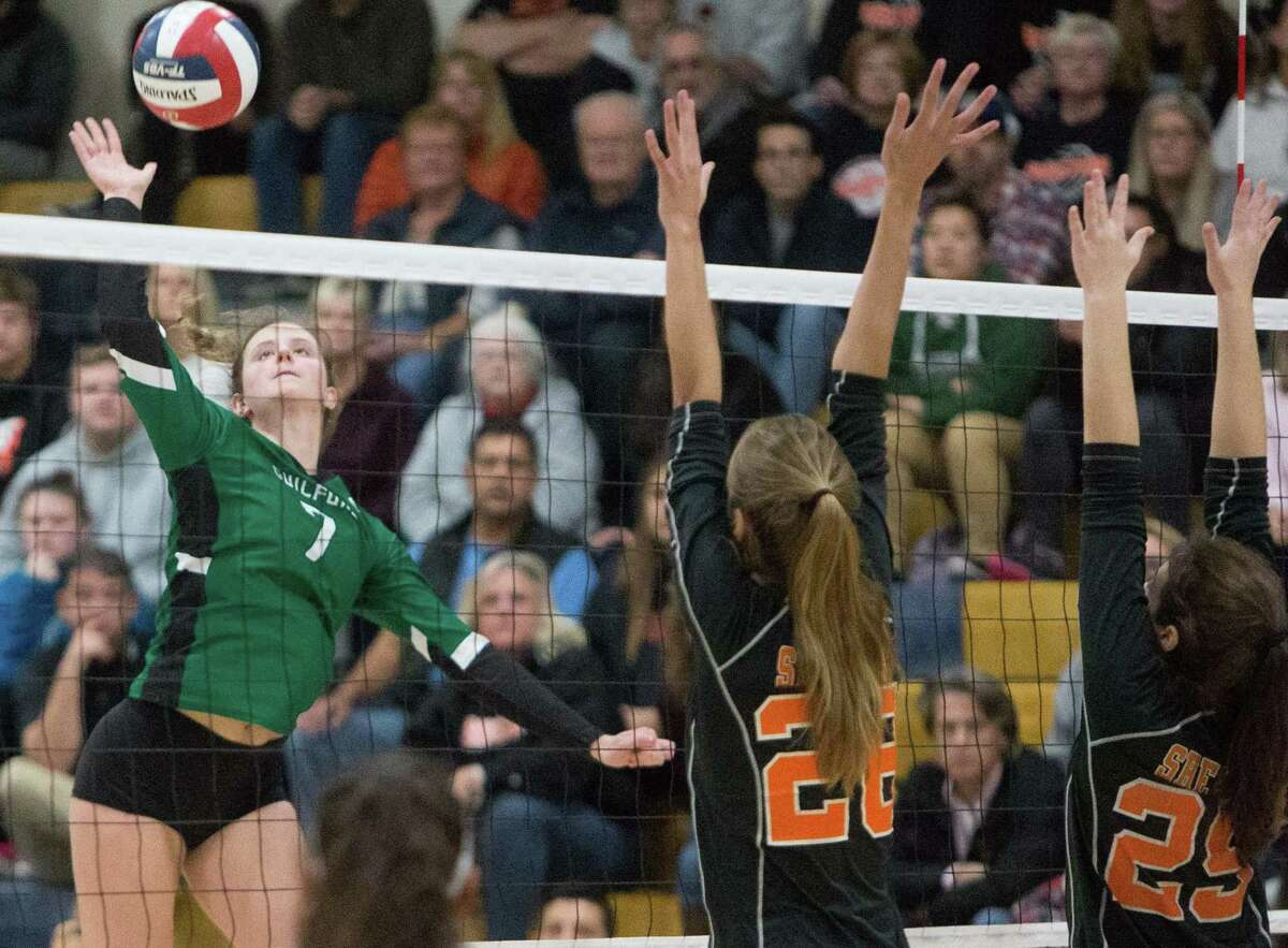 (John Vanacore/FOr Hearst Connecicut Media) Guilford's Emma Appleman goes for the kill over Shelton's Greta Gelumbakickas (28) and Isabella Gillotti (29) during the SCC championship game Saturday night.