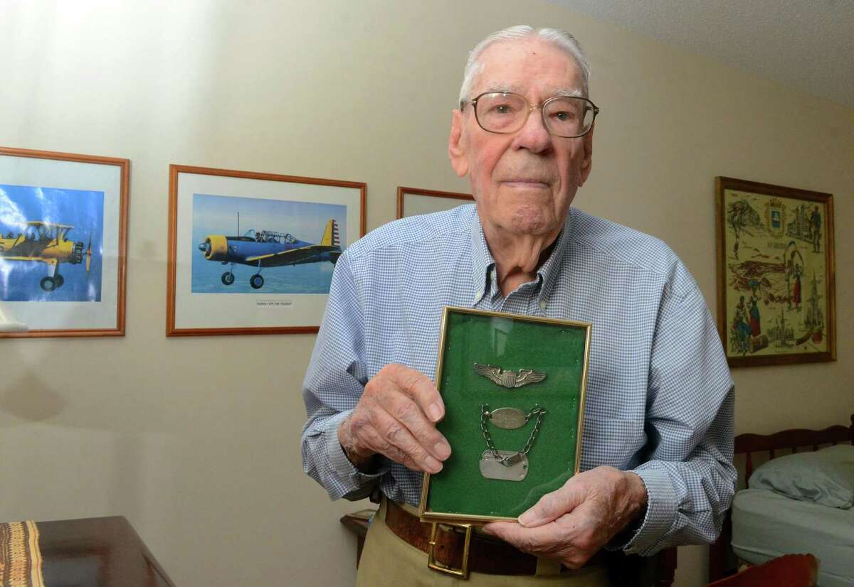 World War II veteran Robert Hart poses with his silver wings and dog tags at his home in North Branford, Conn., on Friday Nov. 8, 2019. Hart flew a C-47 cargo plane that towed a glider carrying troops that landed behind enemy lines on D-Day. During the push to Berlin, Hart flew supplies and fuel as part of the allies supply line as well as transporting injured men back to England.