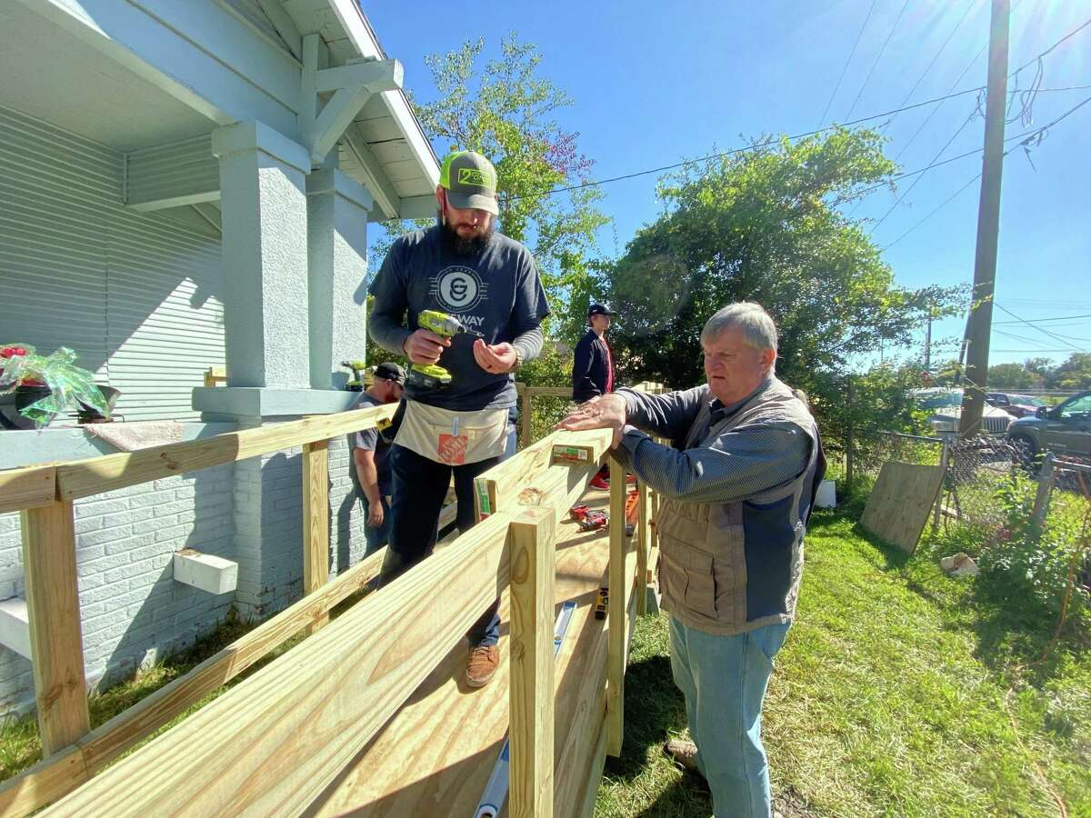 Correy Walters, left, and John Laine help build a ramp at a home on Avenue B in Beaumont on Saturday.
