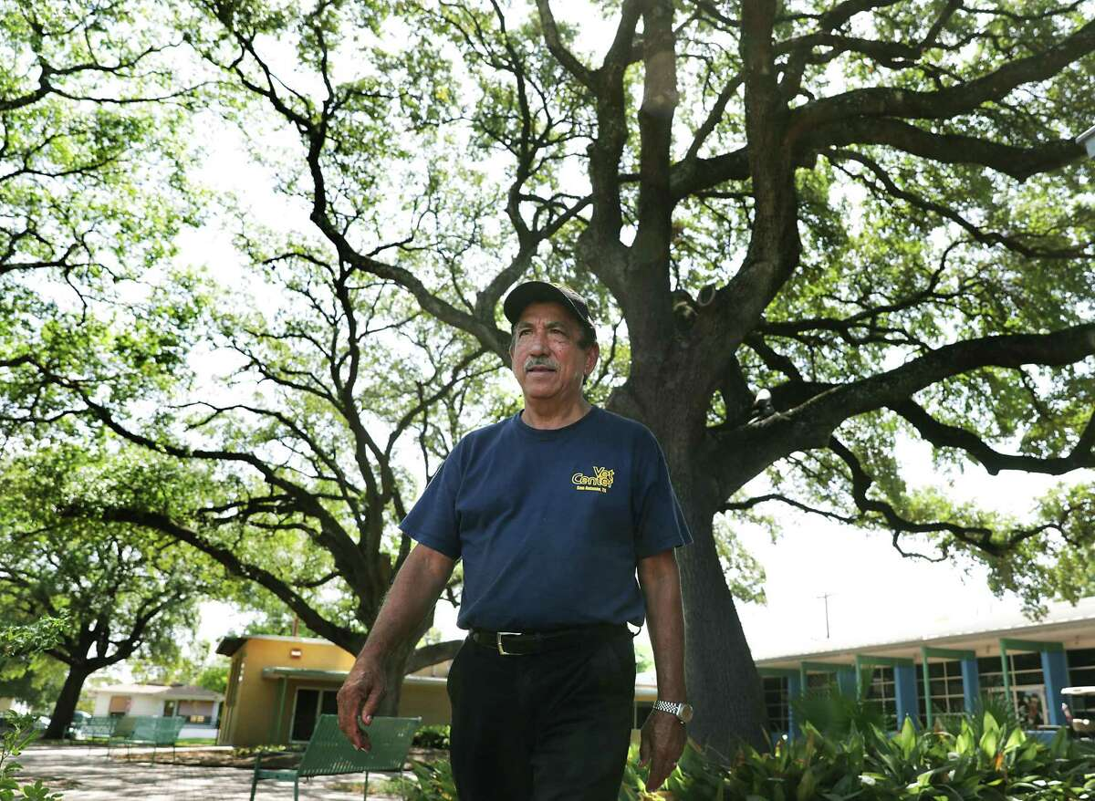 Army veteran Hector Caldera, a member of the board of directors at Good Samaritan Center, walks under the large oak tree in the center's courtyard that he used to climb when he was a kid.