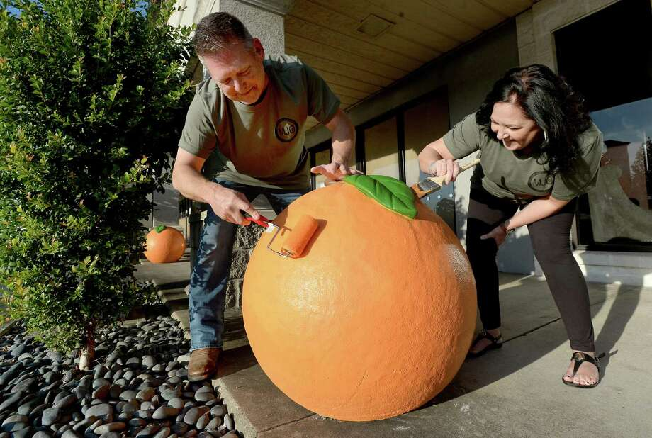 Jesse and Tina Romero apply another coat of paint to one of the two orange statuary pieces outside Mathews Jewelers storefront in Orange. Businesses, schools and other venues throughout Orange County will soon be adorned with the individually painted oranges as part of a Greater Orange Chamber of Commerce beautification project. Photo taken Wednesday, November 6, 2019 Kim Brent/The Enterprise Photo: Kim Brent / The Enterprise / BEN