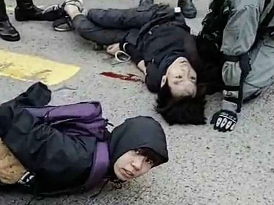 """A video grab taken from Cupid News on November 11, 2019 shows a pro-democracy protester (top) bleeding and lying on the ground after he was shot in the chest by a police man during a protest in Sai Wan Ho district, in Hong Kong. - A Hong Kong police officer shot at masked protesters -- hitting at least one in the torso -- during clashes broadcast live on Facebook, as the city's rush hour was interrupted by protests. (Photo by STRINGER / Cupid News / AFP) / --EDITORS NOTE -- RESTRICTED TO EDITORIAL USE MANDATORY CREDIT """" AFP PHOTO / CUPID NEWS"""" NO MARKETING NO ADVERTISING CAMPAIGNS - DISTRIBUTED AS A SERVICE TO CLIENTS - NO ARCHIVES (Photo by STRINGER/Cupid News/AFP via Getty Images) Photo: STRINGER / AFP or licensors"""
