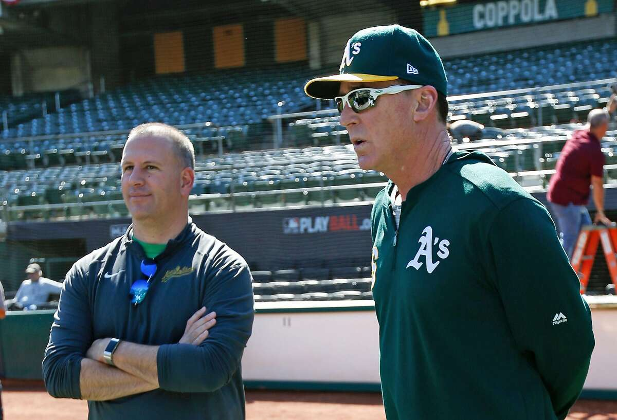 OAKLAND, CA - OCTOBER 1: General Manager David Forst and Manager Bob Melvin #6 of the Oakland Athletics talk on the field during a workout at the Oakland-Alameda County Coliseum on October 1, 2019 in Oakland, California. ~~