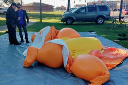 A responding officer and an unidentified man stands by a Baby Trump balloon deflated by someone at Monnish Park as people were protesting President Donald Trump's visit to an NCAA college football game between Louisiana State and Alabama playing nearby in Tuscaloosa, Ala., Saturday, Nov. 9, 2019. The towering Baby Trump protest balloon was knifed and deflated by someone unhappy with its appearance during Trump's trip to Alabama, organizers said. (Stephanie Taylor/The Tuscaloosa News via AP)