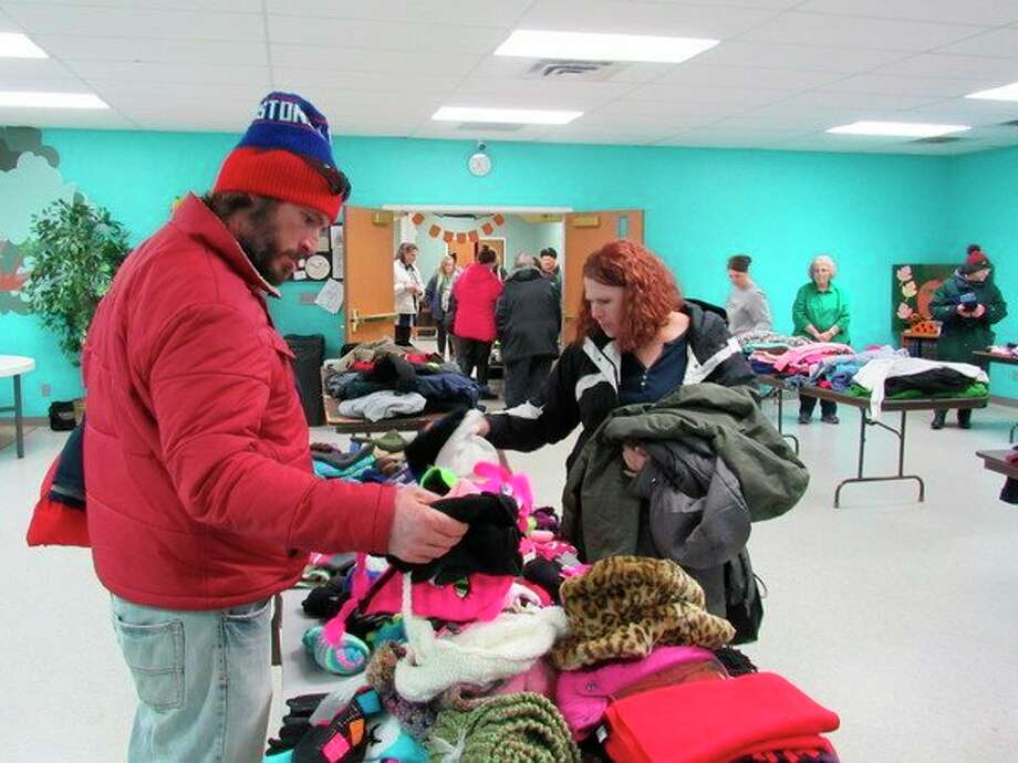 """Thomas, left, and April Debusschere sort through a table of winter clothing accessories at Midland Christian Church's """"Winter Clothing Giveaway."""" (Mitchell Kukulka/Mitchell.Kukulka@mdn.net)."""
