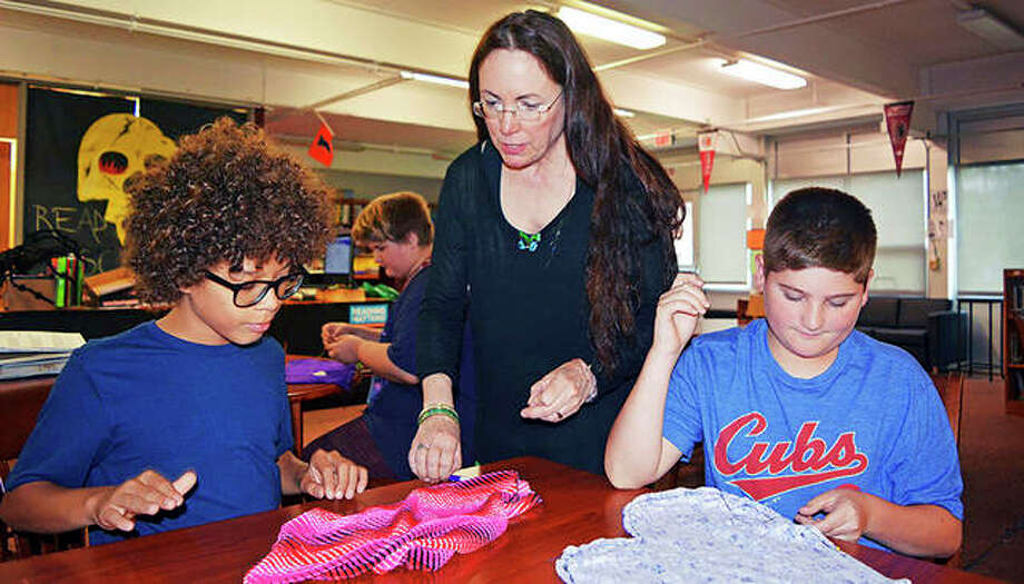North Ridge Middle School librarian Kim Blodgett helps eighth-grader Bryson Cloyd (left) with his pillow while eighth-grader Ethan Fox stuffs his pillow during their lunch period in the school's library in Danville. Photo: Carol Roehm | Commercial-News (AP)