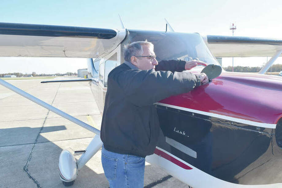 Kent Allen of Jacksonville checks on his plane — an Aero Commander Lark — at the Jacksonville Municipal Airport. Allen has given more than 200 free flights on his plane as part of the Experimental Aircraft Association's Young Eagles program.