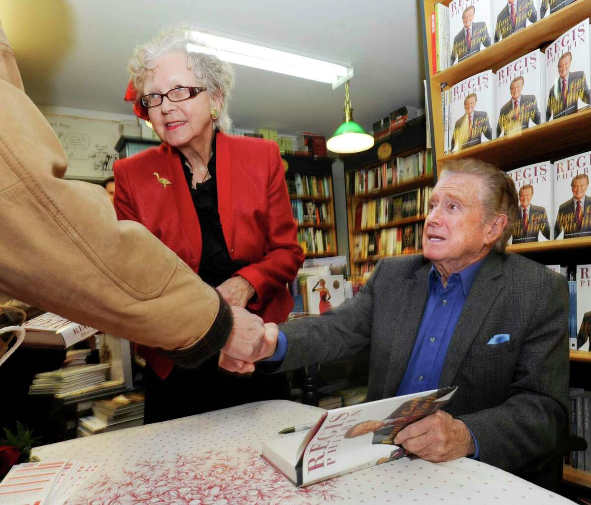 Greenwich resident Regis Philbin, seated, shakes the hand of a fan after signing a copy of his new memoir