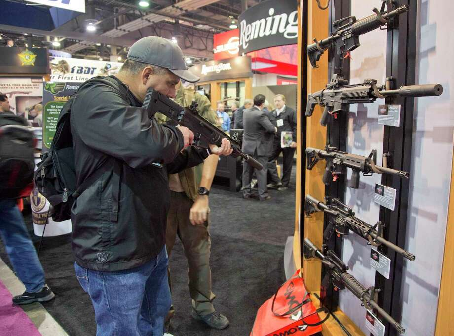 A gun show attendee sights a Remington weapon at a 2013 gun show in Las Vegas organized by the Newtown, Conn.-based National Shooting Sports Foundation. As a group of Newtown parents continue their litigation to hole Remington liable for the 2012 Sandy Hook massacre, Reuters reported that a hedge fund has taken over debt owed by the gun maker. Photo: Julie Jacobson / (AP Photo /Julie Jacobson) / Associated Press