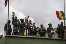 Bolivian national police officers waves to the population from the rooftop of their HQ near Presidential Palace in the capital La Paz, Bolivia, on Nov. 9, 2019.