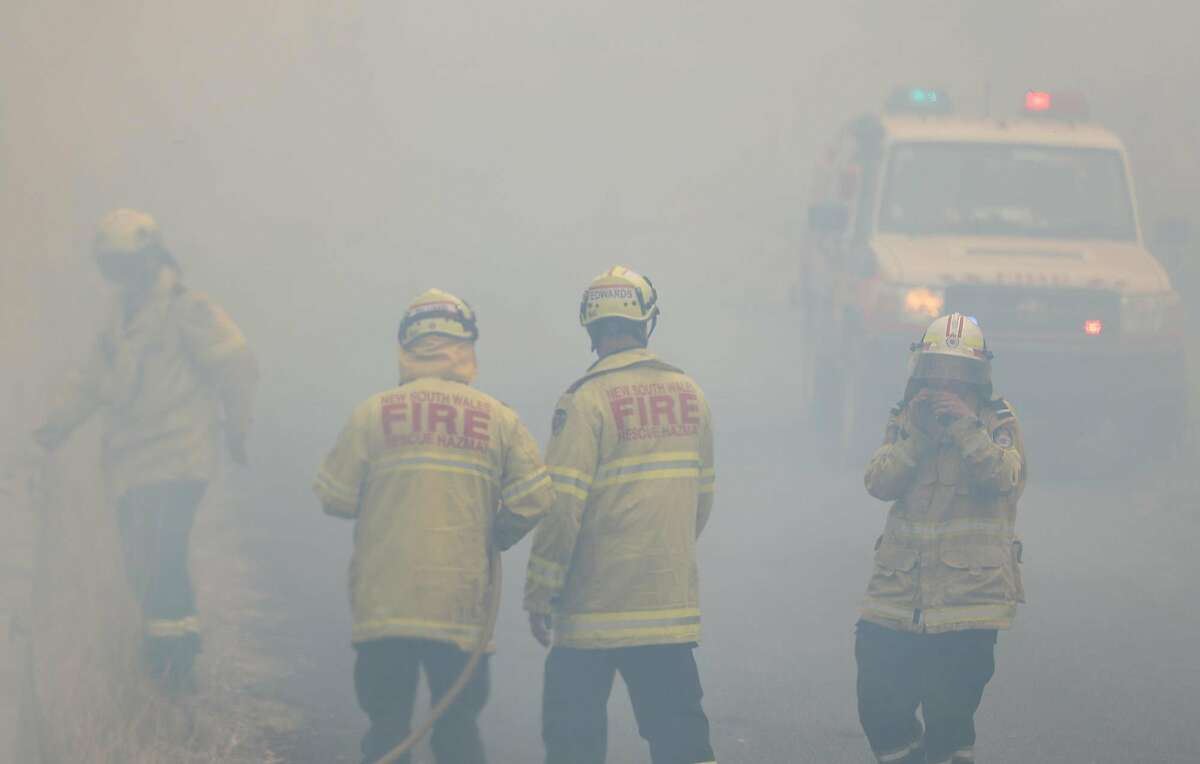 """Firefighters take a break in smoke while battling bushfires near Taree, New South Wales, Australia on Monday, Nov. 11, 2019. A devastating start to the Australian bushfire season has prompted a state of emergency in the eastern state of New South Wales, with the country's largest city, Sydney, bracing for """"catastrophic"""" fire danger. (Bai Xuefei/Xinhua/Zuma Press/TNS)"""