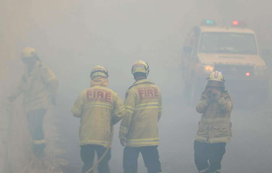 "Firefighters take a break in smoke while battling bushfires near Taree, New South Wales, Australia on Monday, Nov. 11, 2019. A devastating start to the Australian bushfire season has prompted a state of emergency in the eastern state of New South Wales, with the country's largest city, Sydney, bracing for ""catastrophic"" fire danger. (Bai Xuefei/Xinhua/Zuma Press/TNS) Photo: Bai Xuefei/Xinhua, TNS"