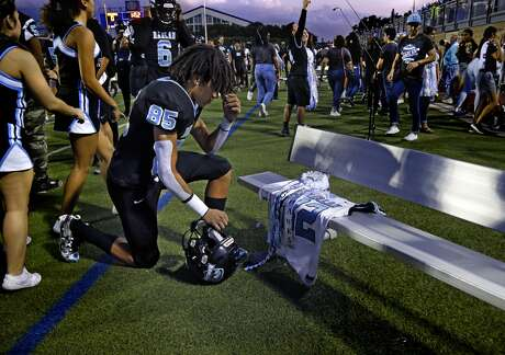 Kamali Anderson kneels for a moment in front of the jersey of his brother Shomari Anderson,82.  After running onto the field with the jersey Anderson placed the jersey on the bench. Harlan was playing Harlandale on Friday, October 4, 2019 at Farris Stadium.  Shomari Anderson died in an automobile accident in the spring.