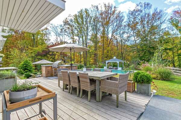 This property features a patio, raised wood deck, hot tub, outdoor shower, fire pit, and new outdoor kitchen.