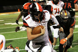 Edwardsville QB Ryan Hampton (3) stays inbounds after breaking a tackle on a 23-yard run in the third quarter Saturday in a Class 8A second-round playoff football game at Minooka.