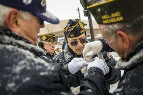 Bill Alderson, left, and Jim Kazmierski, right, help Pat Tracy, center, to put his gloves on before serving in the honor guard during a Veterans Day ceremony Monday, Nov. 11, 2019 at the Midland Veterans Memorial. (Katy Kildee/kkildee@mdn.net)