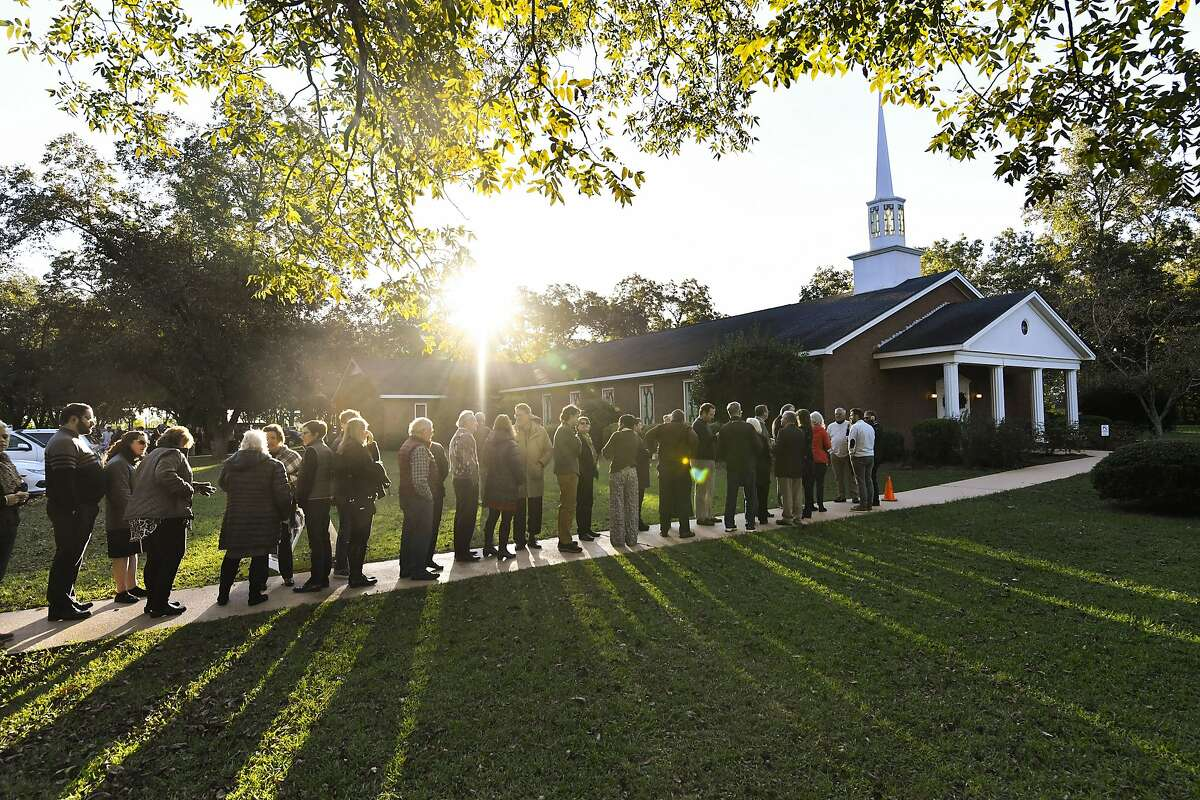 In this Sunday, Nov. 3, 2019, photo, the sun breaks the horizon as guests begin lining up to attend Sunday school class being taught by former President Jimmy Carter at Maranatha Baptist Church, in Plains, Ga. Guests begin arriving before dawn, some even the day before, spending the night in the parking lot, with hopes of attending the class. (AP Photo/John Amis)